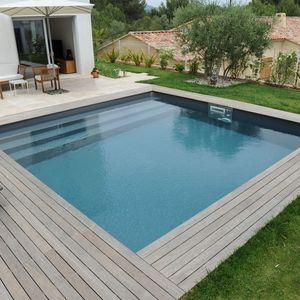 Une piscine carrée Piscinelle face à une maison moderne