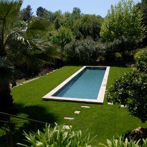 Piscine en forme de bassin de nage traditionnel équipé d'une belle margelle en pierre naturelle et d'un liner gris ardoise au milieu d'un gazon verdoyant.